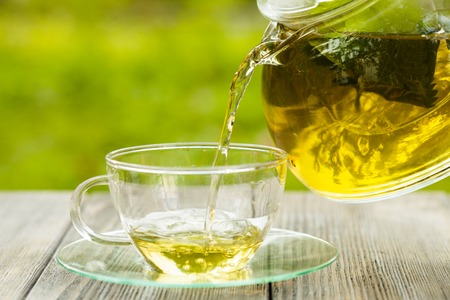 Photo pour Herbal tea in a glass teapot on the table outdoor - image libre de droit