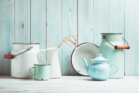 Foto de Enamelware on the kitchen table over blue wooden wall - Imagen libre de derechos