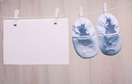 Foto de Baby boy booties attached to the rope and blank card for greetings - Imagen libre de derechos