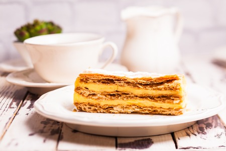 Puff pastry dough with custard cream on a white plate