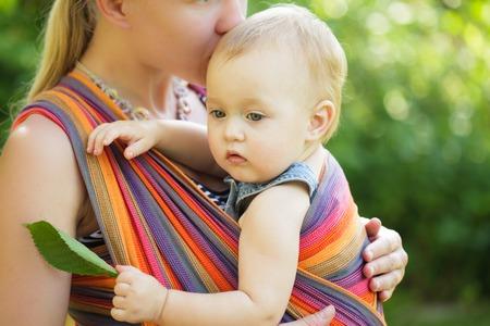 Foto de Baby in sling outdoor. Mother is carrying her child and showing nature details - Imagen libre de derechos