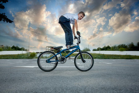 Photo for Close view of young biker doing reckless tricks on bike - Royalty Free Image