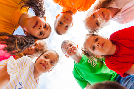 Photo pour Kids standing together in circle looking at the camera - image libre de droit