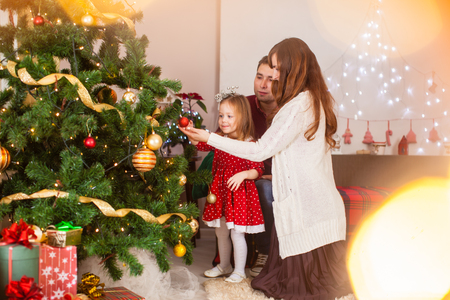 Photo for Happy family with daughter decorate Christmas tree - Royalty Free Image