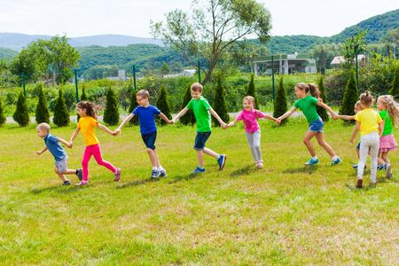 Photo for Kids run holding hands outdoor. Girls and boys have fun - Royalty Free Image