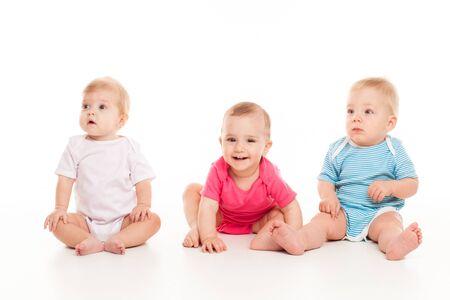 Photo pour Cute babies sitting on white studio background - image libre de droit