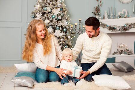 Photo pour Parents sitting on a floor with their child at Christmas eve - image libre de droit
