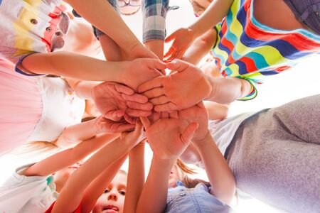 Photo pour Kids are putting hands together, teamwork and friendship, view from the bottom - image libre de droit
