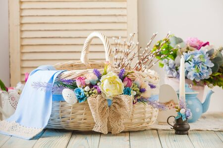 Photo for Side view light pastel Easter wicker basket, decorated with multicolor flowers and laces on a wooden surface and light wood background. Easter concept - Royalty Free Image