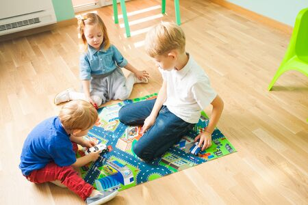Photo pour Children playing with cars on a road themed carpet. Kids at home or daycare. - image libre de droit