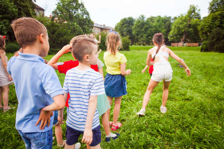 Photo for Back view of a group of kids standing in a line and racing on a green lawn under the supervision of a teacher - Royalty Free Image