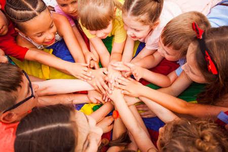 Photo pour Children holding hands together, laying on a floor - image libre de droit