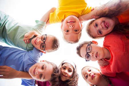 Photo pour Smiling kids embracing together in a circle - image libre de droit