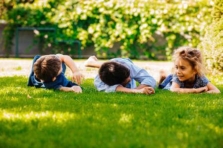 Photo pour Portrait of three little children lying on a green grass - image libre de droit
