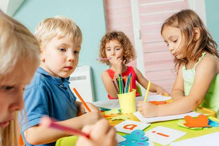 Photo pour Preschool children learn english alphabet using cards - image libre de droit