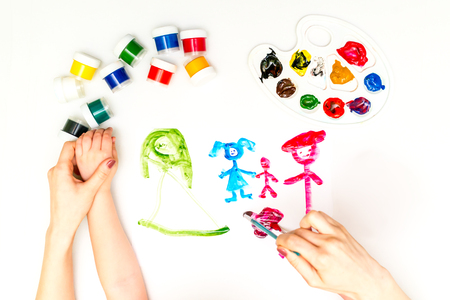 Photo pour Childs hands painting a family - image libre de droit
