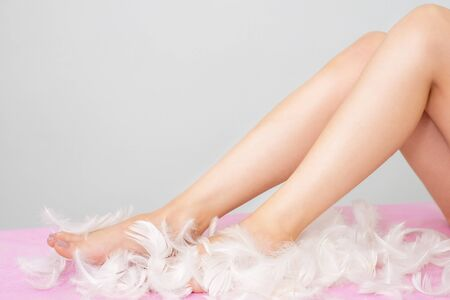 Photo pour Closeup of long woman legs in feathers with perfect hairless smooth and silky skin. - image libre de droit