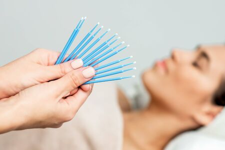 Photo for Eyelash cotton swabs in hands, eyelash extension disposable microbrushes on background of patient, close up. - Royalty Free Image