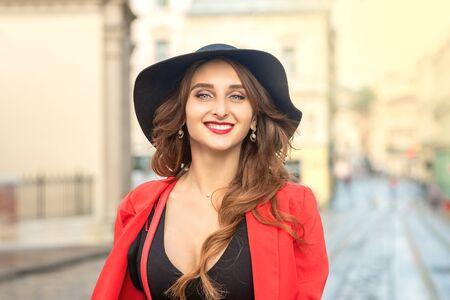 Photo pour Outdoor portrait of young elegant fashionable woman wearing trendy hat walking in street of European city. - image libre de droit