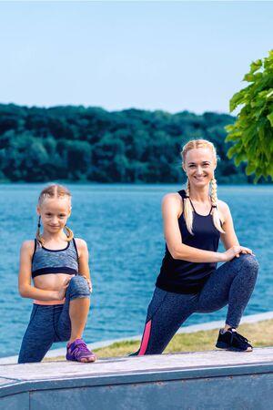 Foto de Portrait of mother and child in sport style clothes on the shore of the lake. - Imagen libre de derechos