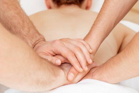 Photo pour Back massage of woman in four hands by two massage therapists in massage salon. - image libre de droit