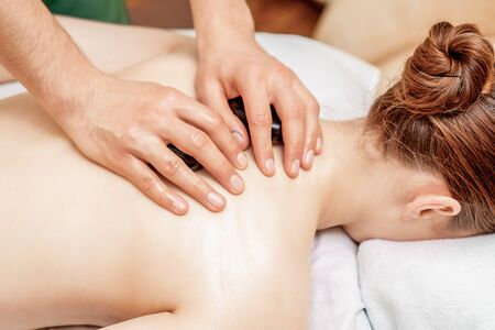 Photo pour Young woman receiving a stone massage on back while hands of massage therapist puts stones on her back. - image libre de droit