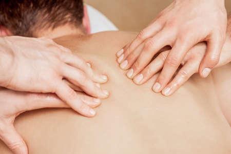 Photo pour Close-up of massage therapists hands massaging man's back in spa. - image libre de droit