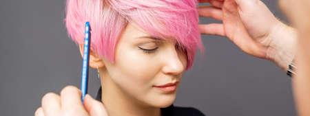 Foto für Hairdresser checking short pink hairstyle of young woman on gray background - Lizenzfreies Bild