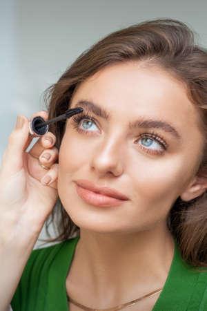Photo pour Professional makeup artist applying mascara on lashes of beautiful young caucasian woman in beauty salon - image libre de droit