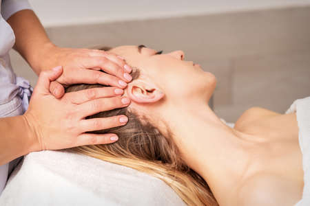 Photo pour Young woman receiving head massage by hands of beautician in spa beauty center - image libre de droit