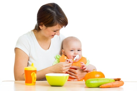 young mother spoon feeding her baby girl isolated on white