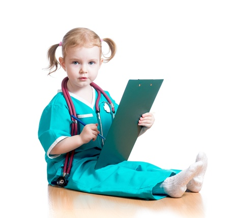 Child girl uniformed as doctor writing to clipboard isolated on white