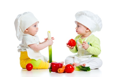 Foto de babies boy and girl wearing a chef hat with healthy  food vegetables - Imagen libre de derechos