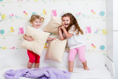 children sisters playing in bedroom