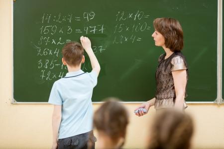 Photo pour School kids in classroom at math lesson - image libre de droit
