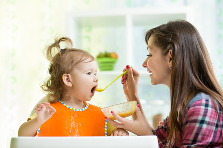 Mother feeding kid with spoon indoors