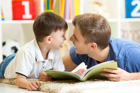 Photo pour father and his kid son reading a book on floor at home - image libre de droit