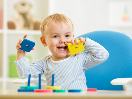 little baby boy playing with building blocks
