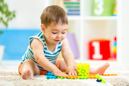 child boy plays with block toys indoor