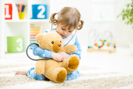 Foto de Cute kid girl playing doctor with plush toy at home - Imagen libre de derechos
