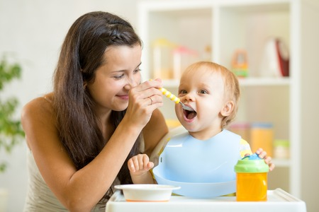 Beautiful young woman feeds child baby boy