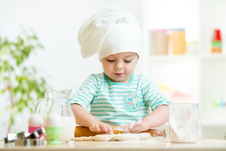 little baker kid girl in chef hat at kitchenの写真素材