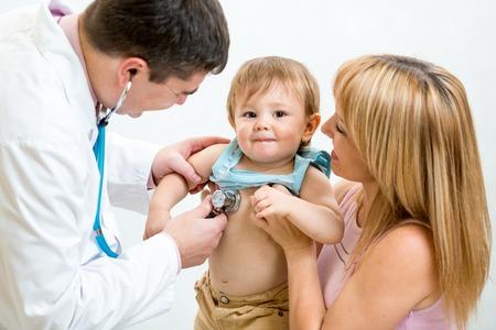 Photo pour Pediatrician doctor examining kid boy. Mother holding baby. - image libre de droit