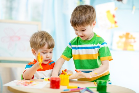 kids playing and painting at homeor kindergarten or playschool or daycare