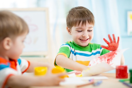 smiling kids playing and painting at home or kindergarten or playschool