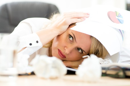 Businesswoman under pile of documents surrounded crumpled papers