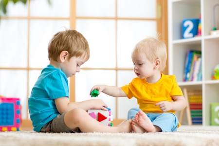 two children boys play together educational toys in playroom