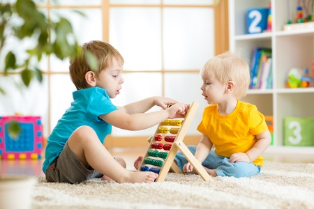 Foto de children boys play with abacus toy indoors - Imagen libre de derechos