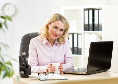 Cute blond mature businesswoman working on laptop and drinking coffee