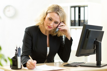Middle-aged businesswoman working in office. Employee talking by phone and writing by pen
